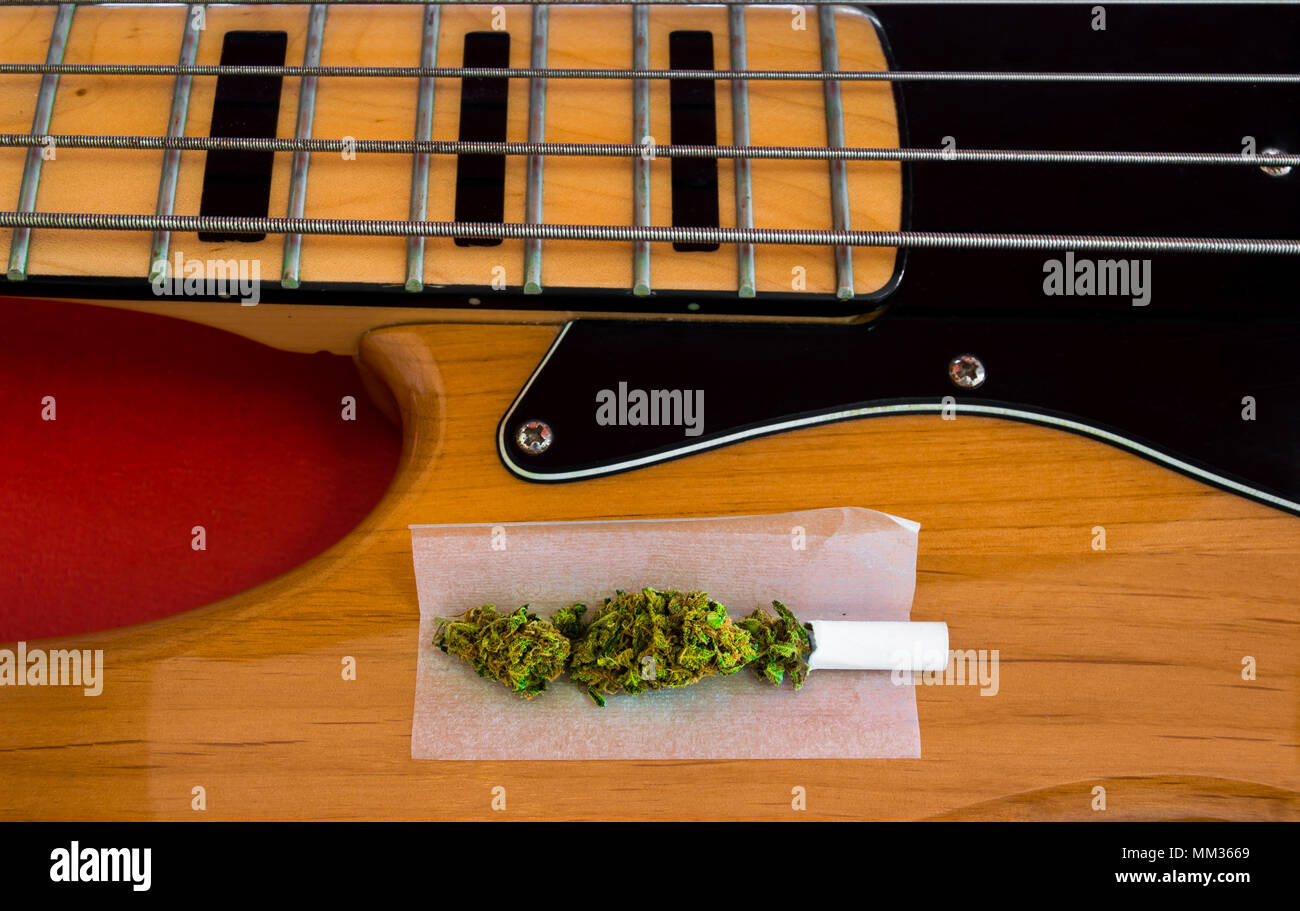 Marijuana joint ready to roll on vintage electric bass of four strings. Musical instrument and drugs, concept of look for inspiration. - Stock Image
