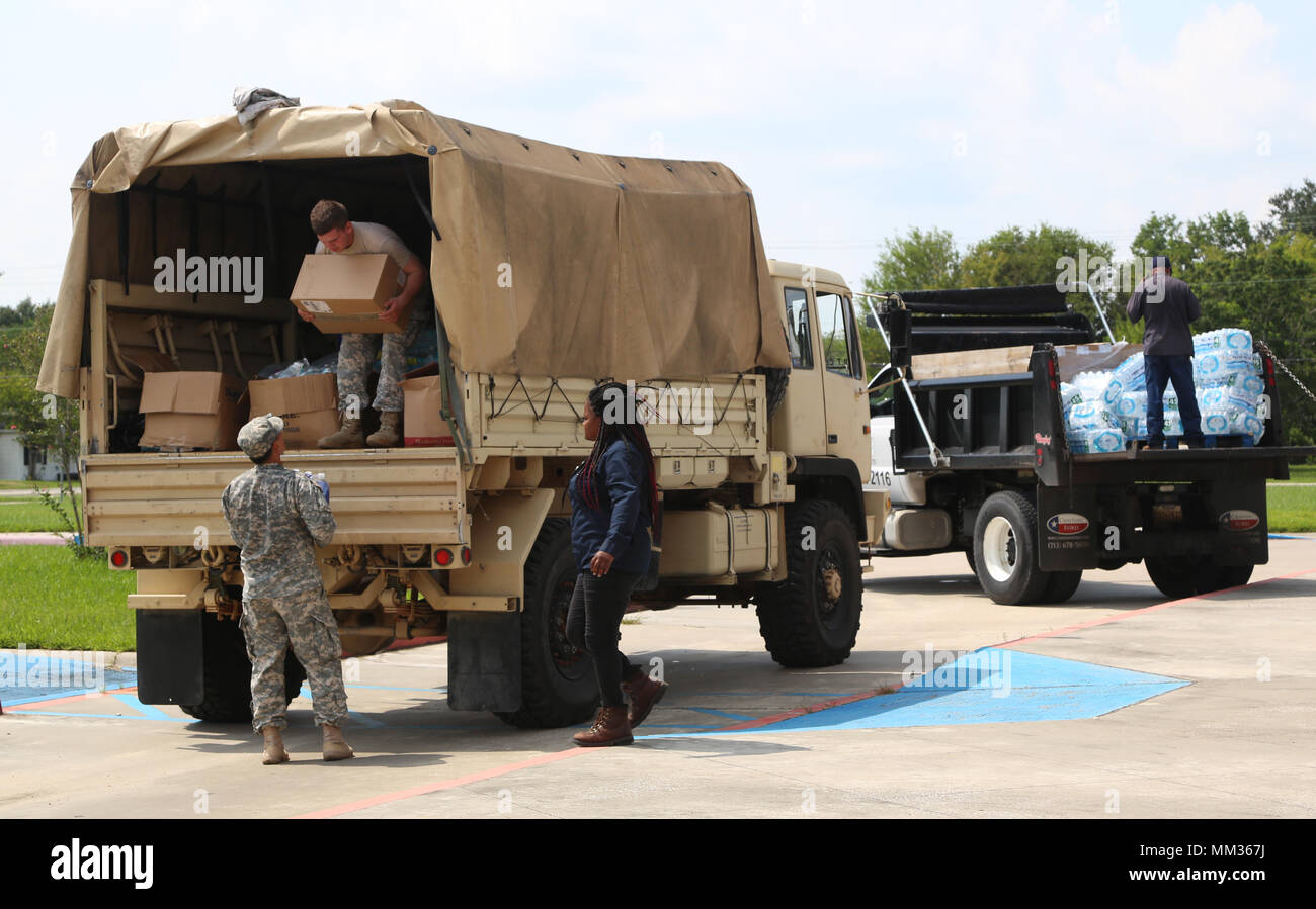 U.S. Army Sgt. Jonghyeong Lee, left, and Spc. Elert Nicholas, Chemical, Biological, Radiological and Nuclear Specialists, assigned to 48th Chemical Brigade, unload care packages at West Side Development Center at Port Arthur, Texas, Sept. 3, 2017. Packaged bottled waters, food, and toiletries were delivered to those affected by Hurricane Harvey.  (U.S. Army photo by Spc. Elizabeth Brown) - Stock Image