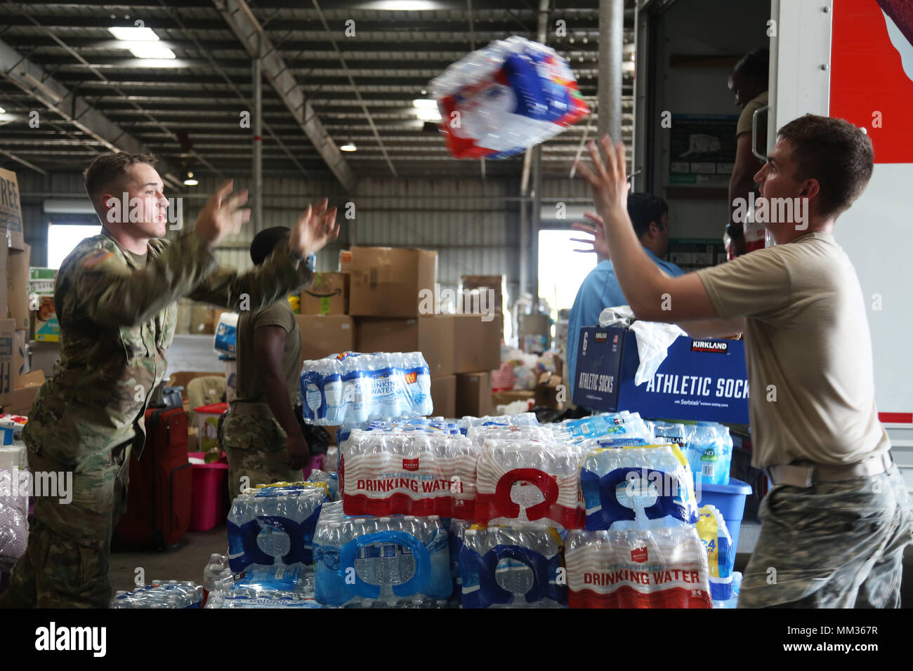 U.S. Army Spc. Trevor Faulkner, Motor Transport Operator, left, and Spc. Elert Nicholas, Chemical, Biological, Radiological and Nuclear Specialist, assigned to 48th Chemical Brigade, unload bottled waters at Port Arthur, Texas, Sept. 3, 2017. Bottled waters, food, and toiletries were delivered out to those affected by Hurricane Harvey.  (U.S. Army photo by Spc. Elizabeth Brown) - Stock Image