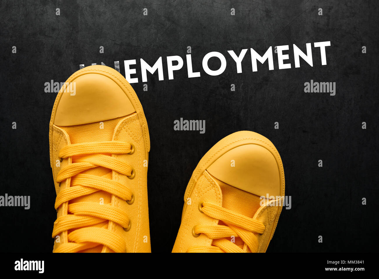 Unemployment concept, young man covering part of the word to make Employment - Stock Image