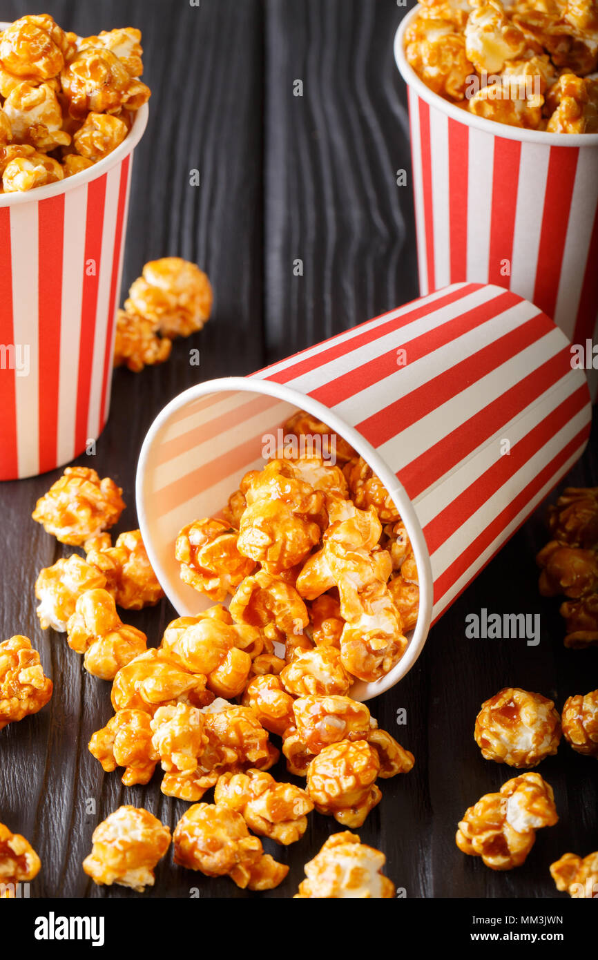 Sweet caramel popcorn in paper cups close-up on the black table. vertical - Stock Image