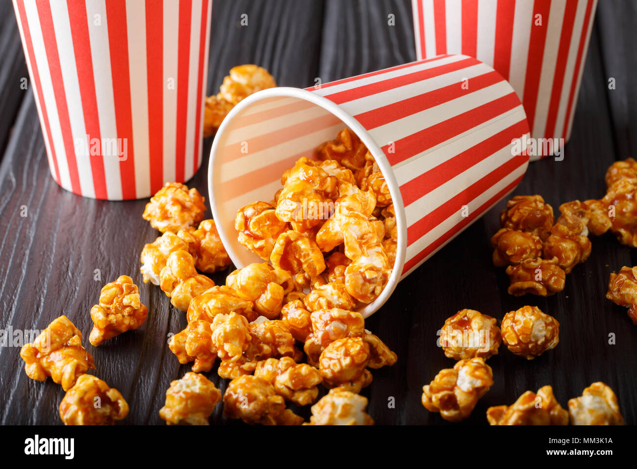 Delicious caramel popcorn in paper cups close-up on the table. horizontal - Stock Image