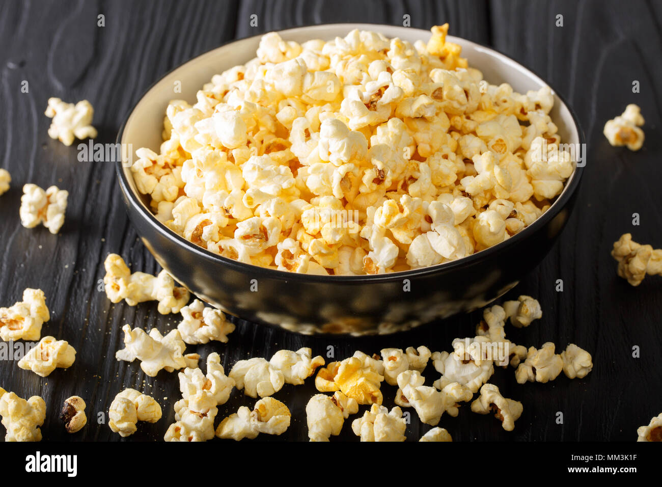 Cheddar cheese salted popcorn closeup in a  bowl on black table. vertical - Stock Image