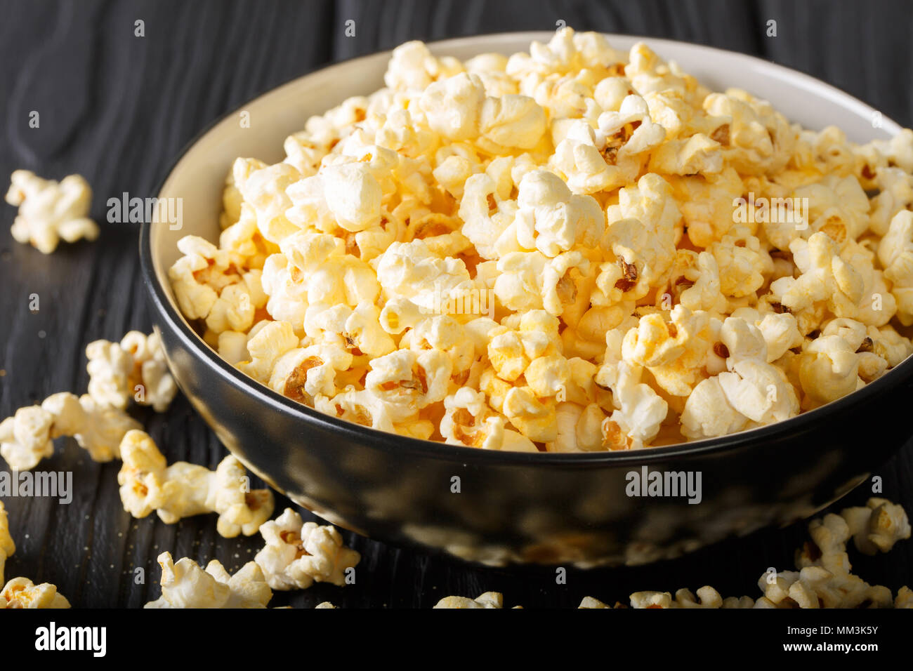 Popular snack: salted popcorn with cheddar cheese and parmesan in a bowl close-up on the table. horizontal - Stock Image