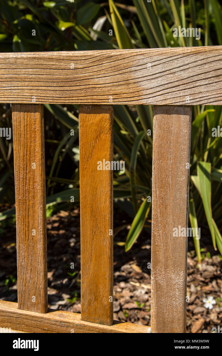 A teak garden bench with teak oil half applied to it\'s uprights ...