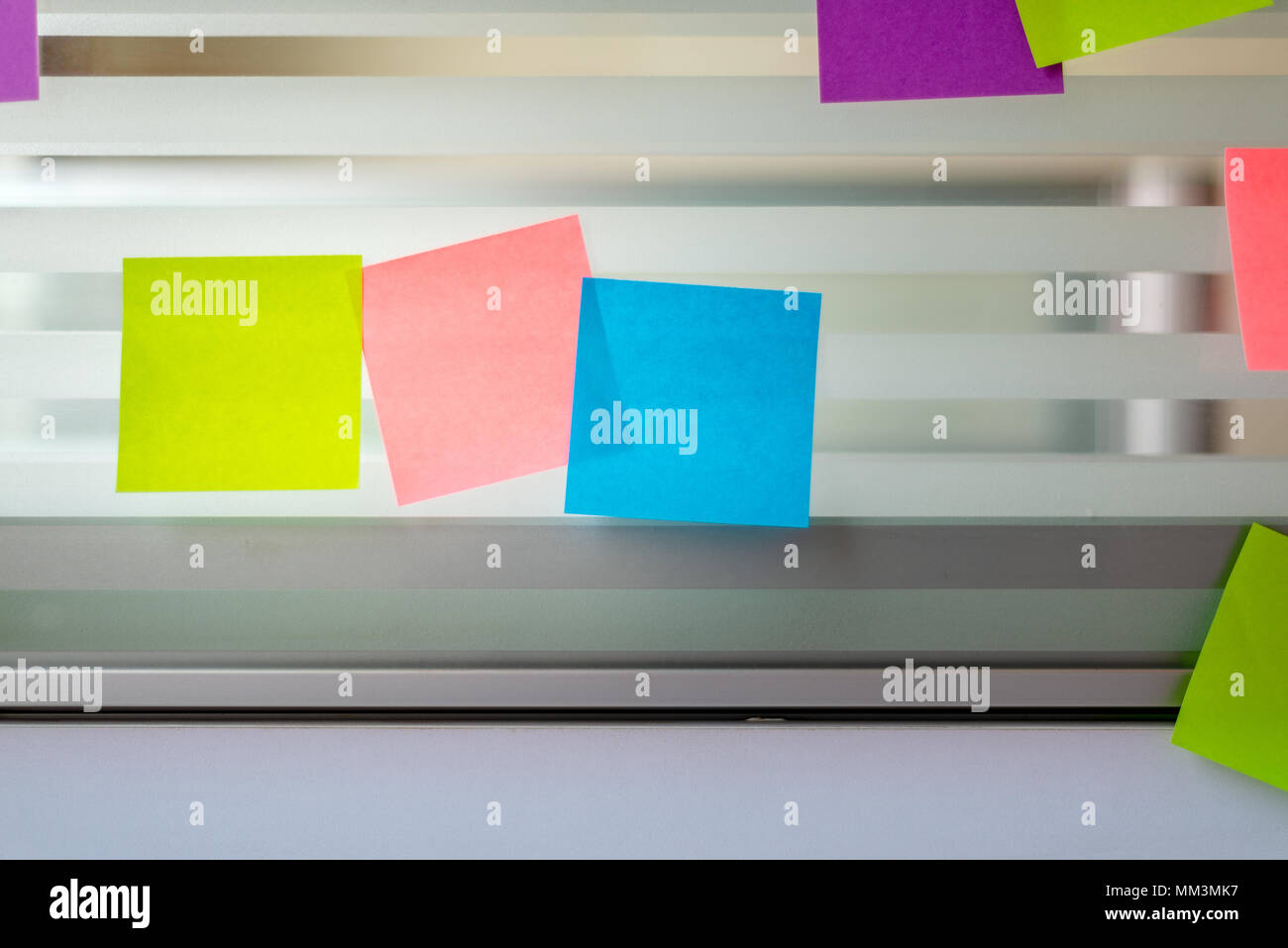 Randomly scattered blank colored sticky notes over glass screen of a bench desk - Stock Image