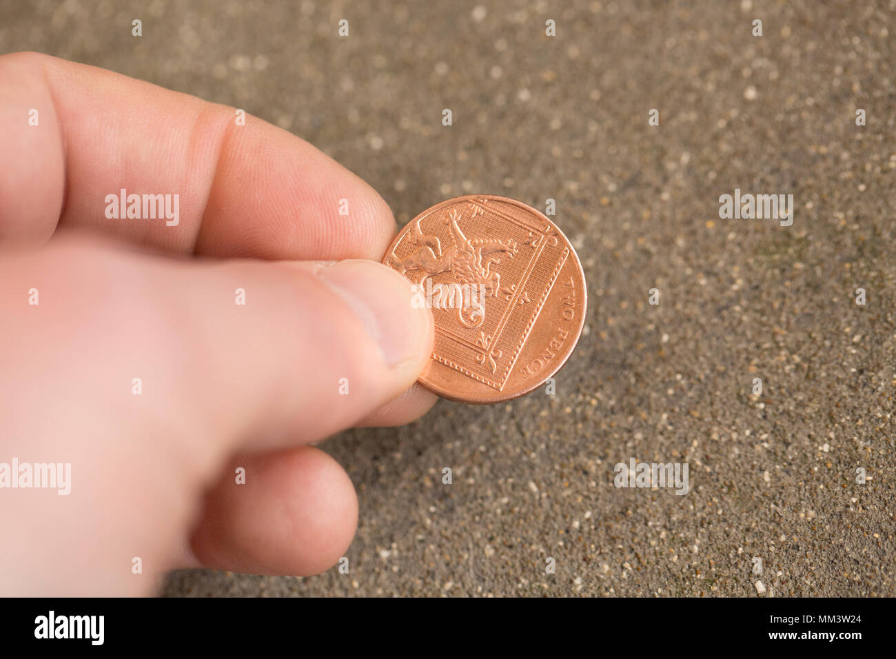 Posed picture of picking up a two pence piece from the ground. UK Stock Photo