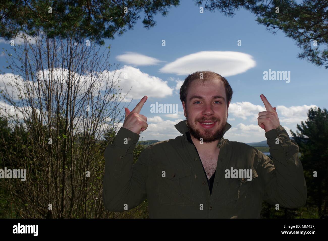 Caucasian Male Adventurer Poses Happily Under Cloud Formation as a Hat. Muir of Dinnet, NNR, Cairngorms, Scotland, UK. May, 2018. - Stock Image