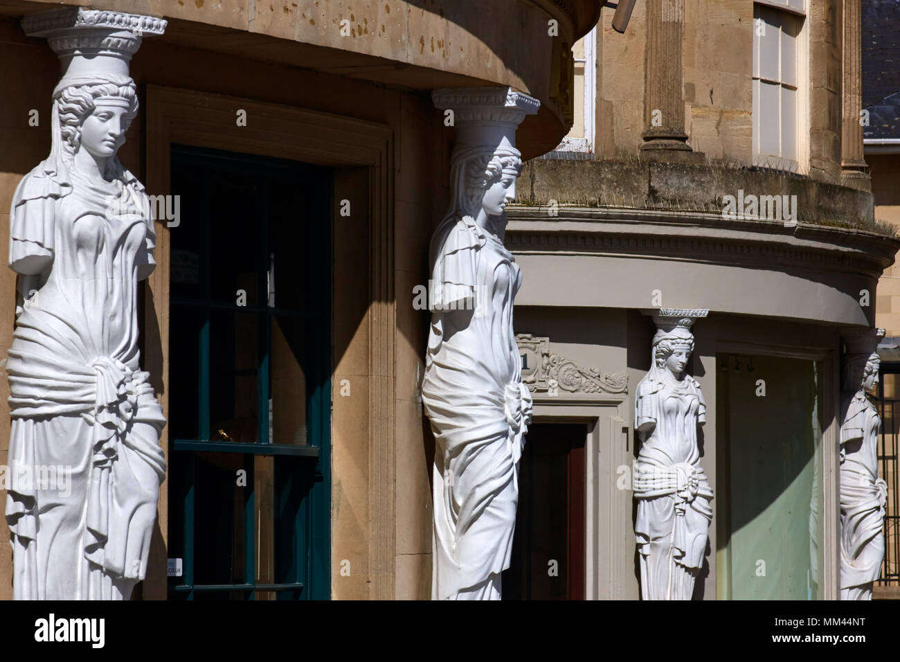 Caryatids architectural feature on shop fronts in the Montpellier district of Cheltenham, Gloucestershire. - Stock Image