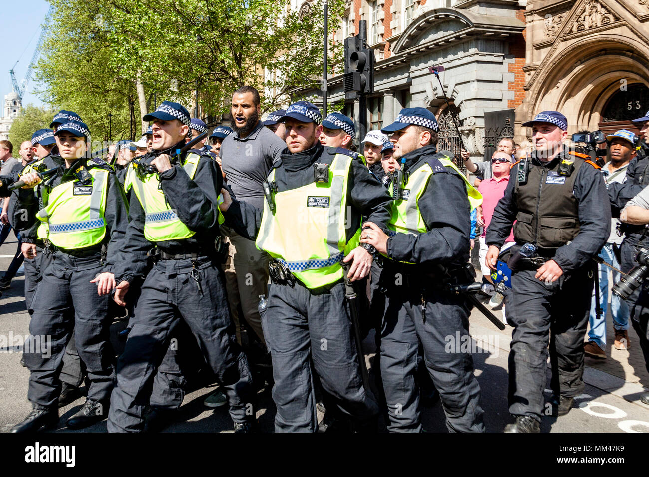 Metropolitan Police Officers escort prominent Muslim speaker Muhammed Hijab away from a freedom of speech rally, London, UK - Stock Image