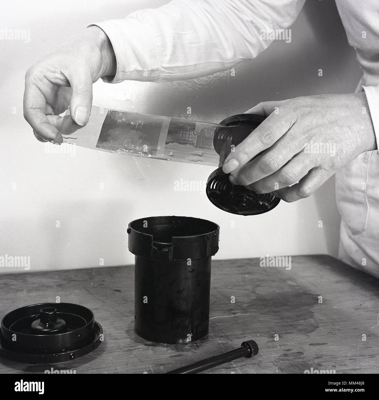 1950s, historical picture showing a strip of film negatives after being taken out of the chemical solution used to develop the black and white photographic film. - Stock Image