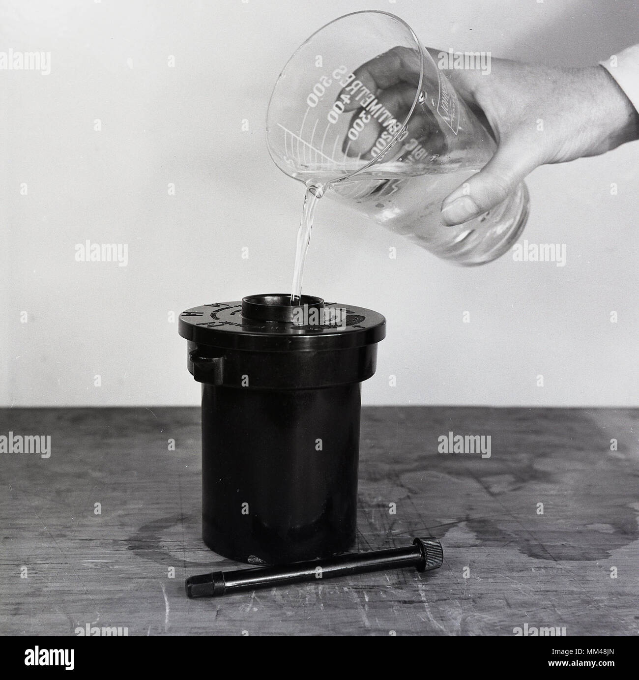 1950s, historical picture showing the chemical solution being added to a container to develop the black and white photographic film. - Stock Image