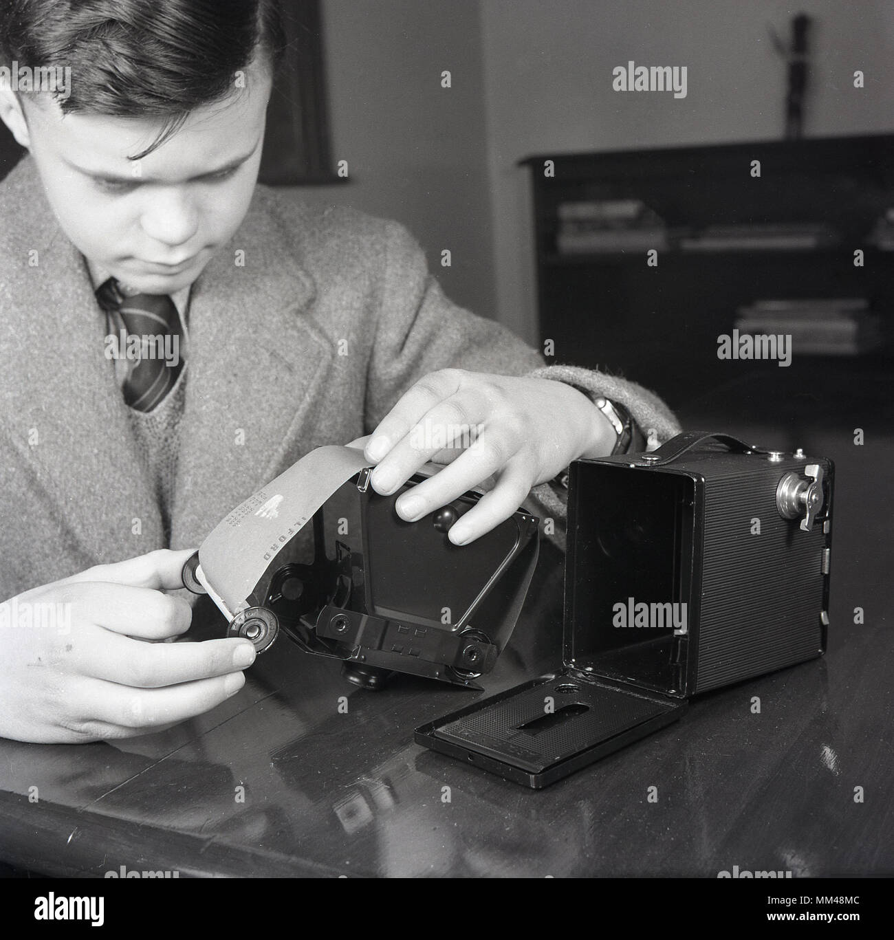 1950s, historical, young schoolboy putting 127 roll film into a Kodak Brownie film camera. Simple and inexpensive, this was one of the most important cameras in history as it brought the concept of the 'snapshot' to the mass market and was especially popular with children - Stock Image