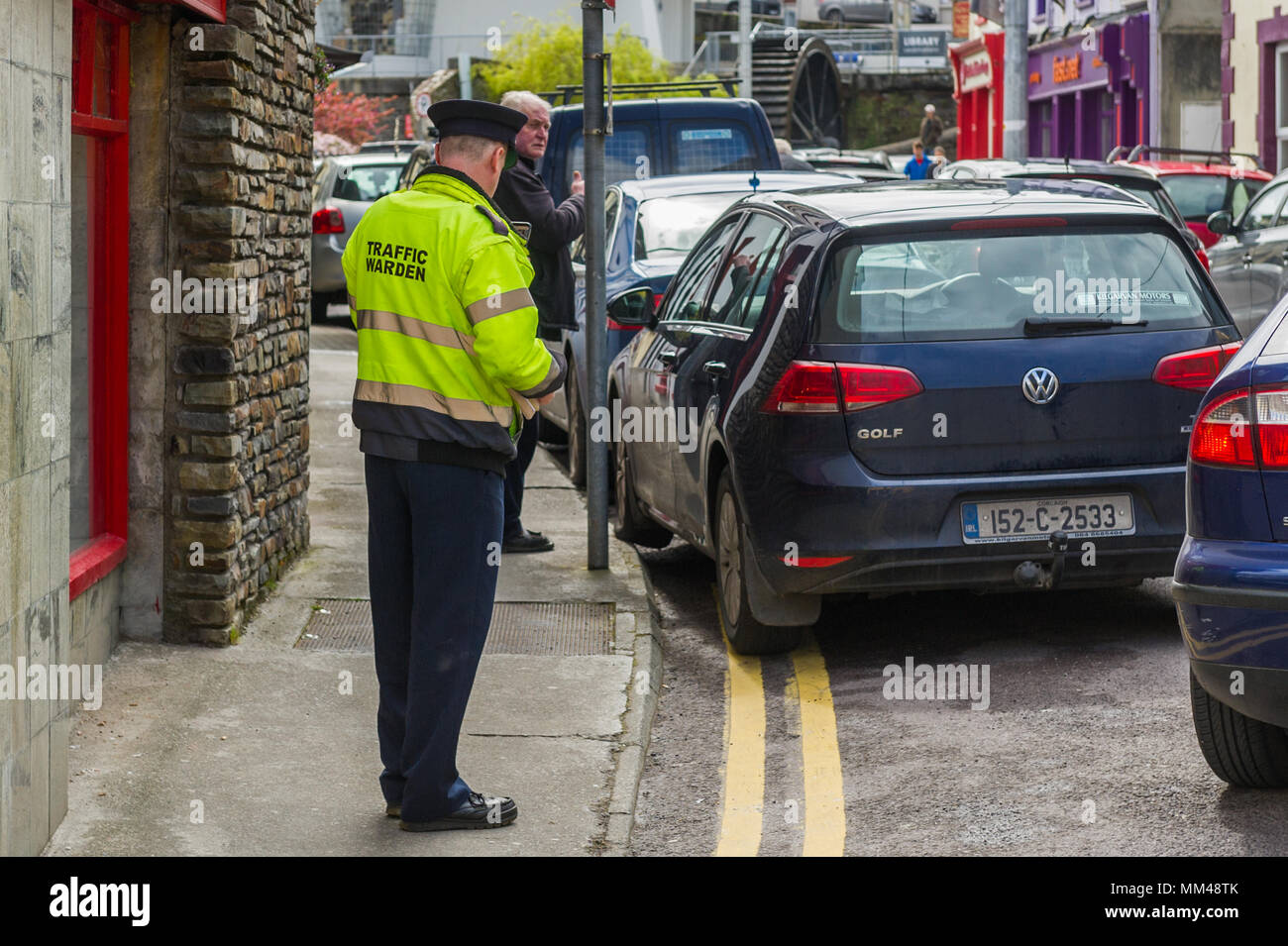 Irish Traffic Warden issues a parking ticket to a car which is parked on double yellow lines and the pavement in Bantry, County Cork, Ireland. - Stock Image
