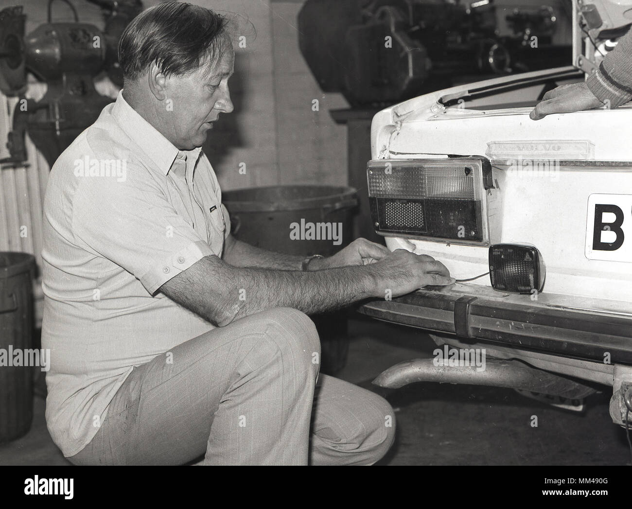 1970s, historical, a man attending an adult education class of car  maintenance or servicing, kneeling down while working on the back lights of a volvo motorcar, England, UK. - Stock Image