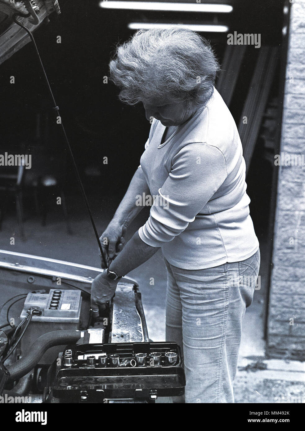 1970s, historical picture showing a mature woman doing an adult educational class of car or motor vehicle maintenance. The bonnet of car is up and she is using a spanner from a toolbox to undo nuts to remove the battery. - Stock Image