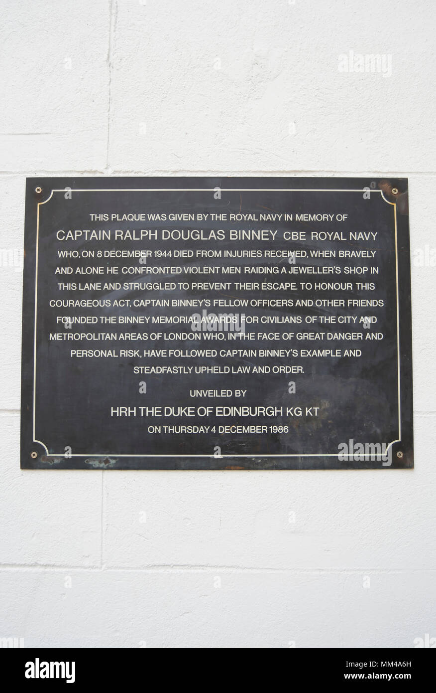 plaque in the city of london noting the bravery of naval captain ralph douglas binney in attempting to thwart a robbery and dying of injuries received - Stock Image