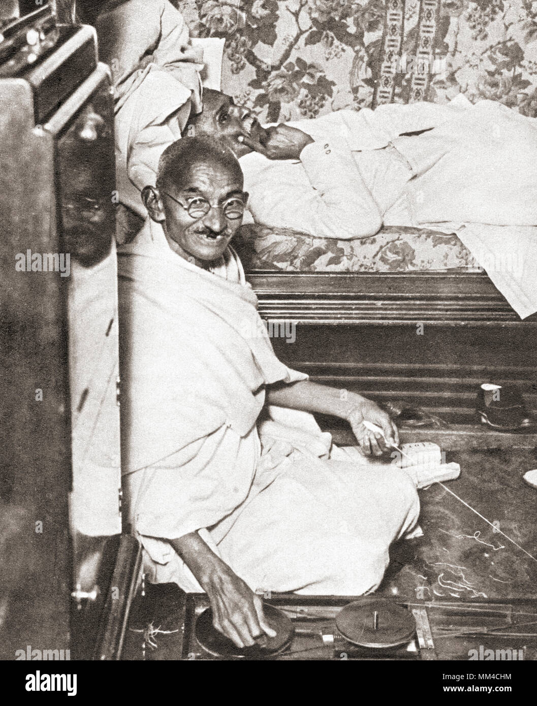 Mohandas Karamchand Gandhi, aka Mahatma Gandhi,1869 – 1948. Indian activist, leader of the Indian independence movement against British rule.  Seen here at the Round Table Conference, 1931. On the floor beside him is his spinning wheel, a symbol of his attempt to resurrect Indian industry at the expense of British trade.  From The Pageant of the Century, published 1934 - Stock Image