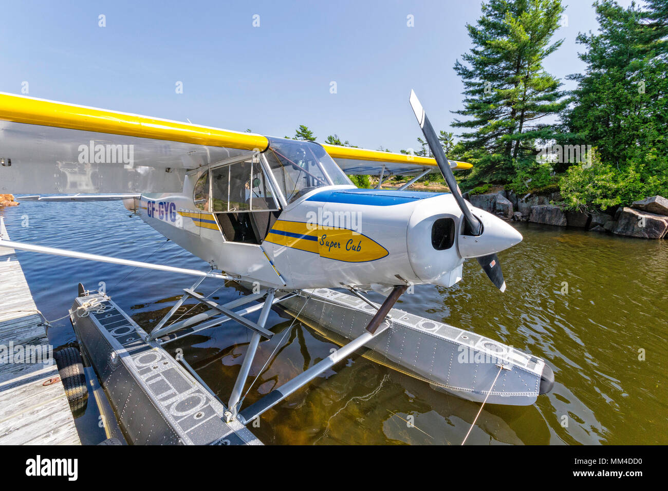 A Piper Super Cub,PA 18 tied to a dock in northern Ontario - Stock Image