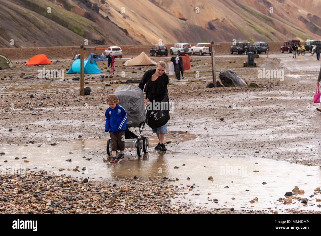Mother and her pram and boy crossing puddles in the campsite in the Landmannalaugar valley, Landmannalaugar,  Fjallabak Nature Reserve, Iceland - Stock Image