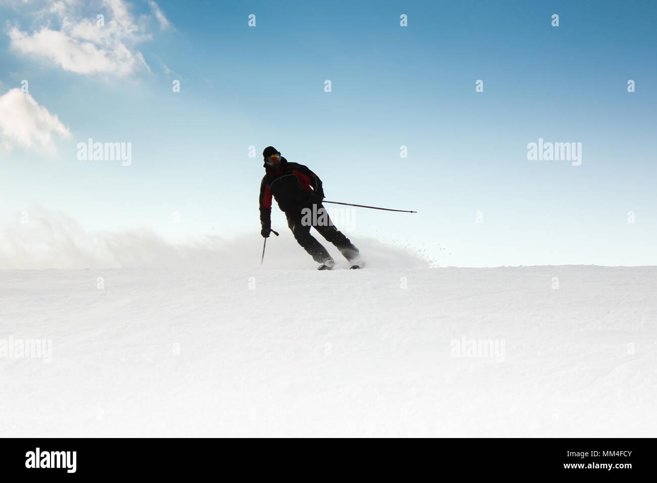 Skier on piste running downhill Stock Photo
