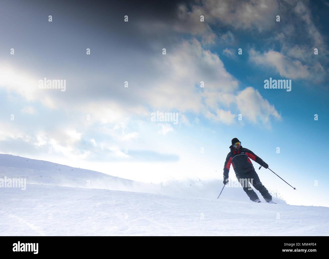 Skier on piste running downhill - Stock Image