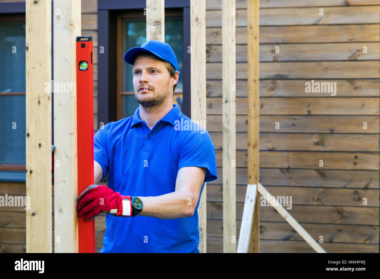 worker check the level of wooden house structure Stock Photo