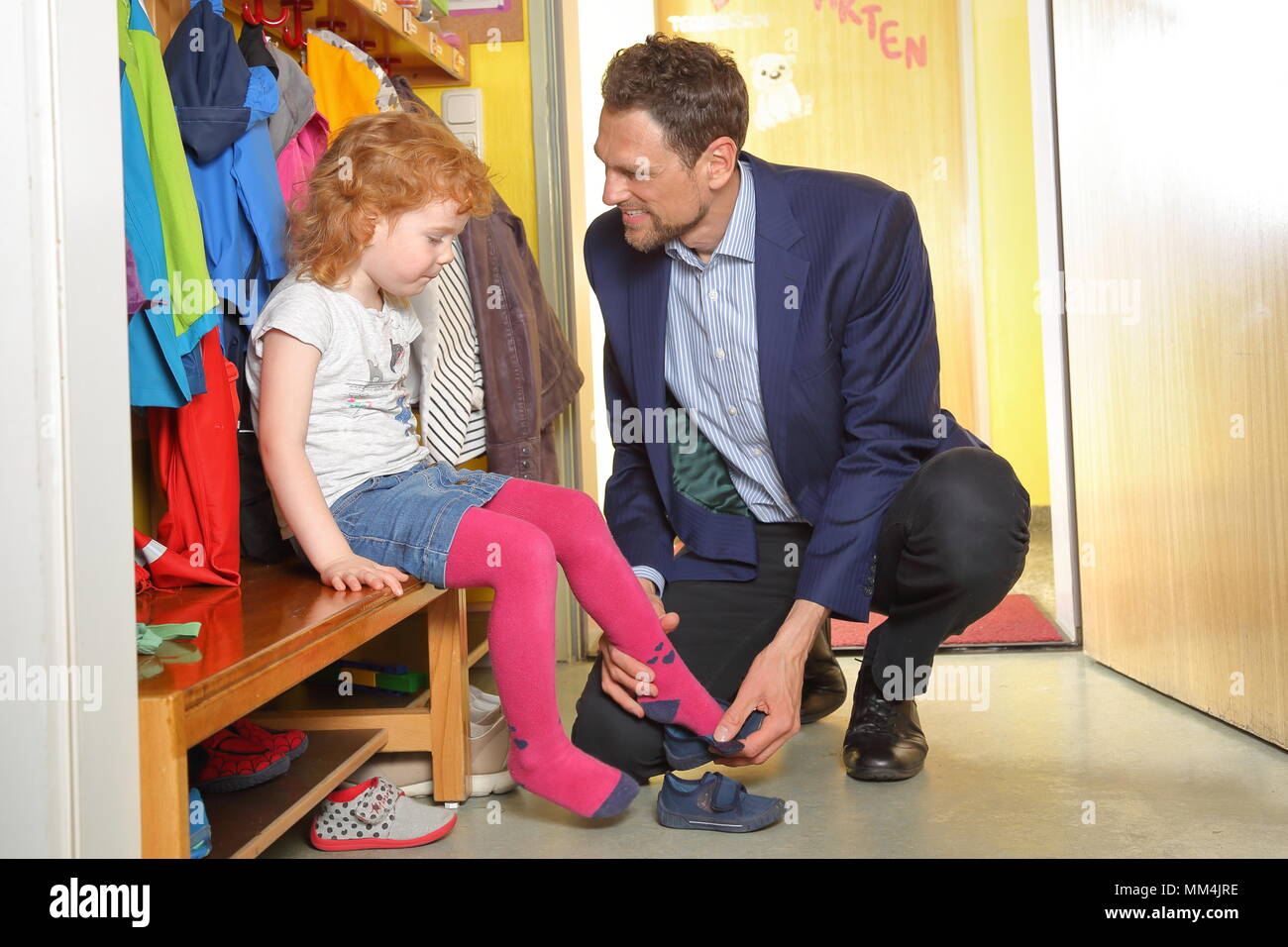 A father picks up his child in nursery - Stock Image