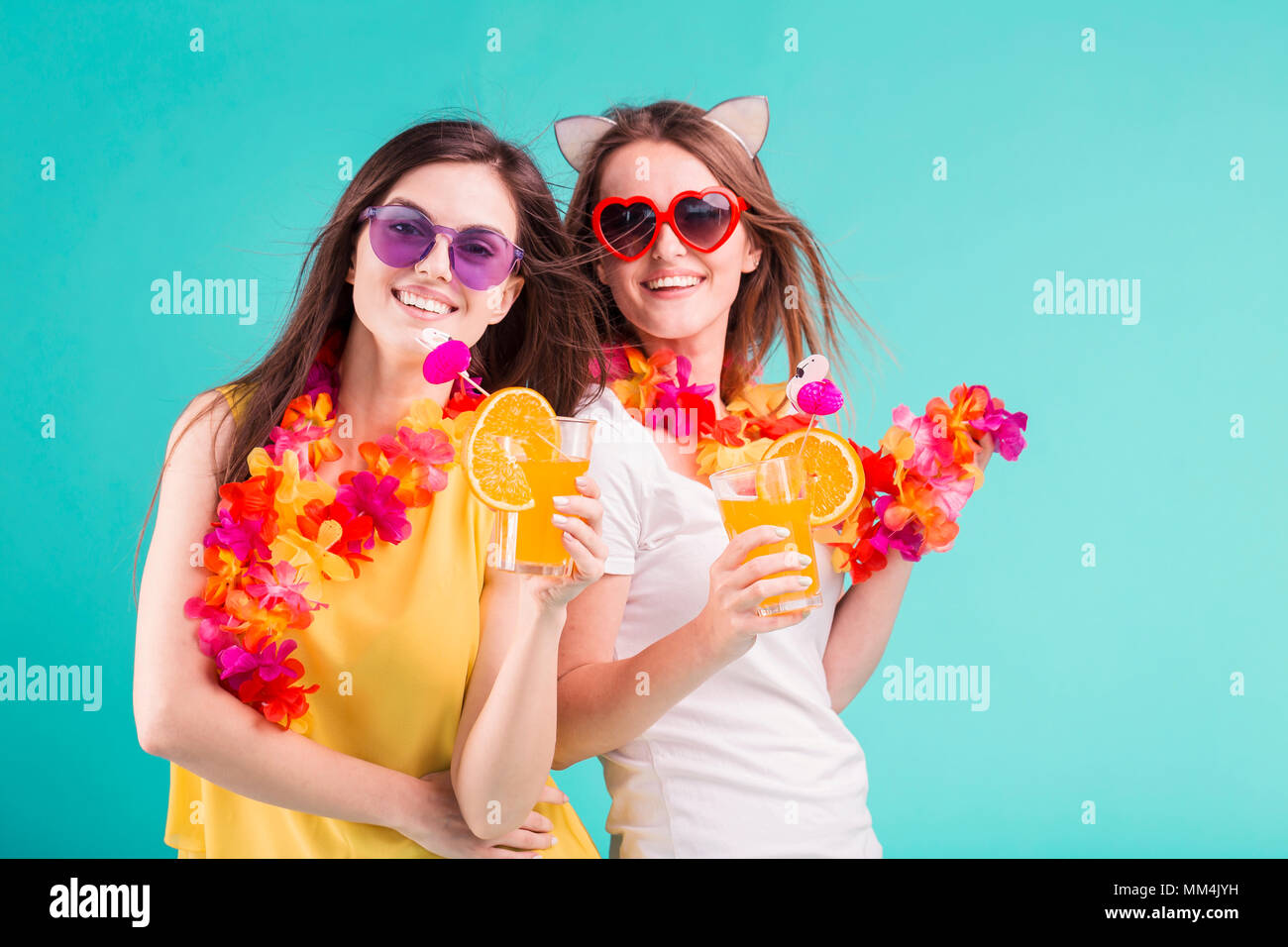 Two pretty smiling caucasian girls wears t-shirts with lei and sunglasses hold orange cocktails on blue background - Stock Image
