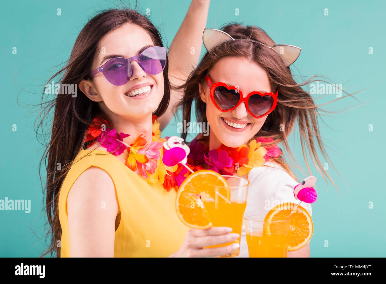 Two beautiful smiling caucasian girls wears t-shirts with lei and sunglasses hold orange cocktails on blue background - Stock Image