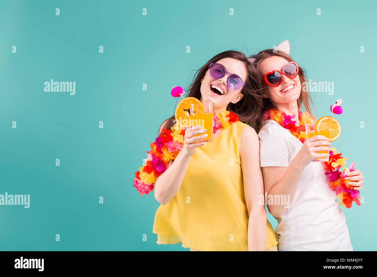 Two beautiful smiling caucasian girls wears t-shirts with lei and sunglasses hold orange cocktails on blue background, summer vacation concept - Stock Image