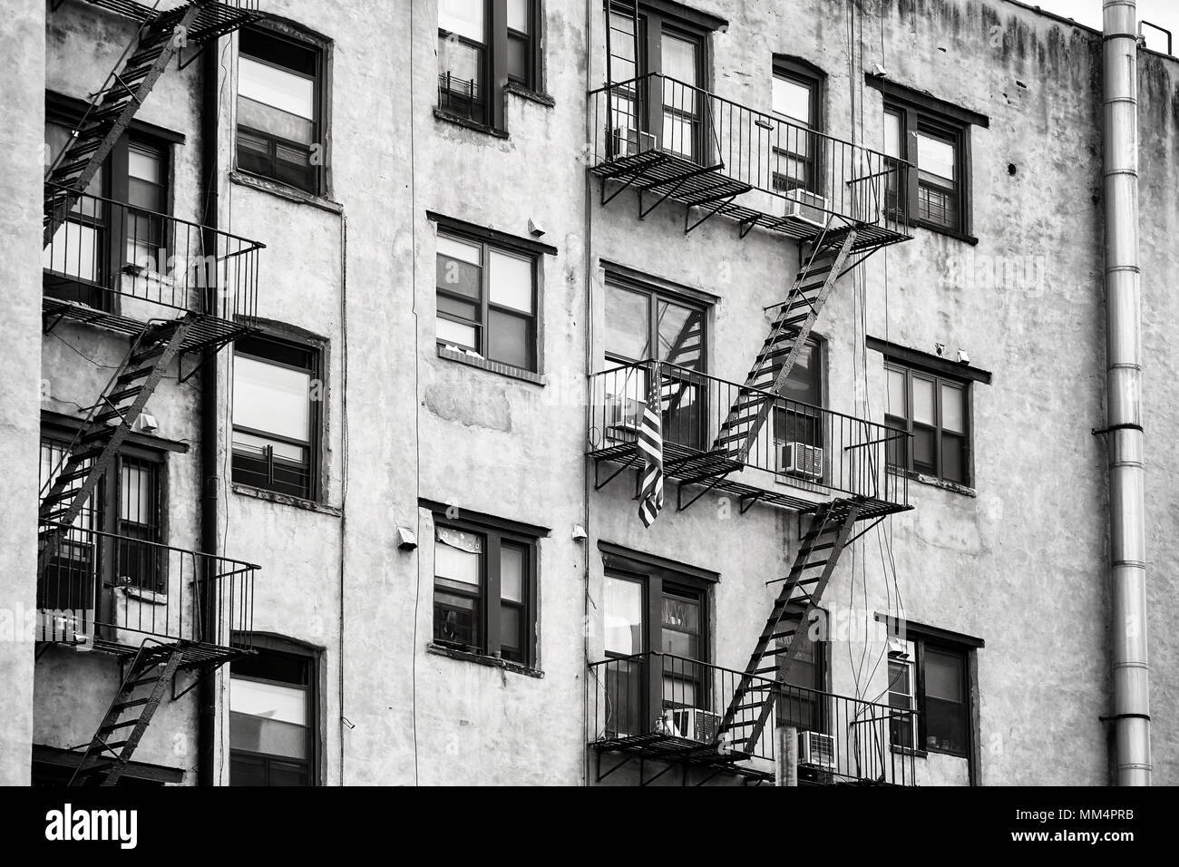 Black and white picture of old building with fire escapes, one of the New York City symbols, USA. - Stock Image