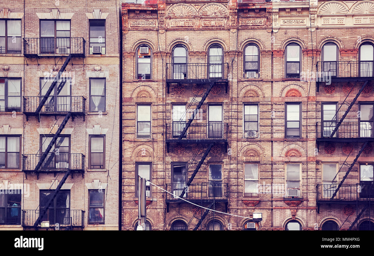 Old buildings with fire escapes, one of the New York City symbols, color toned picture, USA. - Stock Image