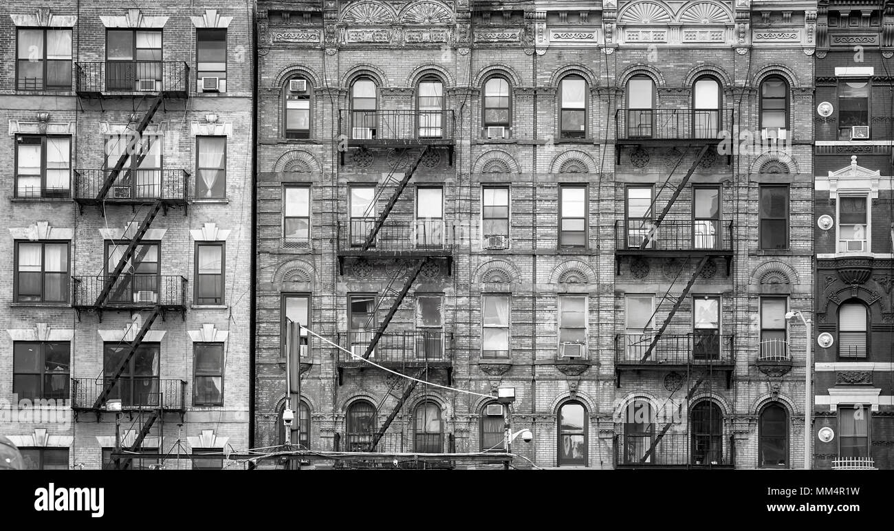 Black and white picture of old buildings with fire escapes one of the new york city symbols usa