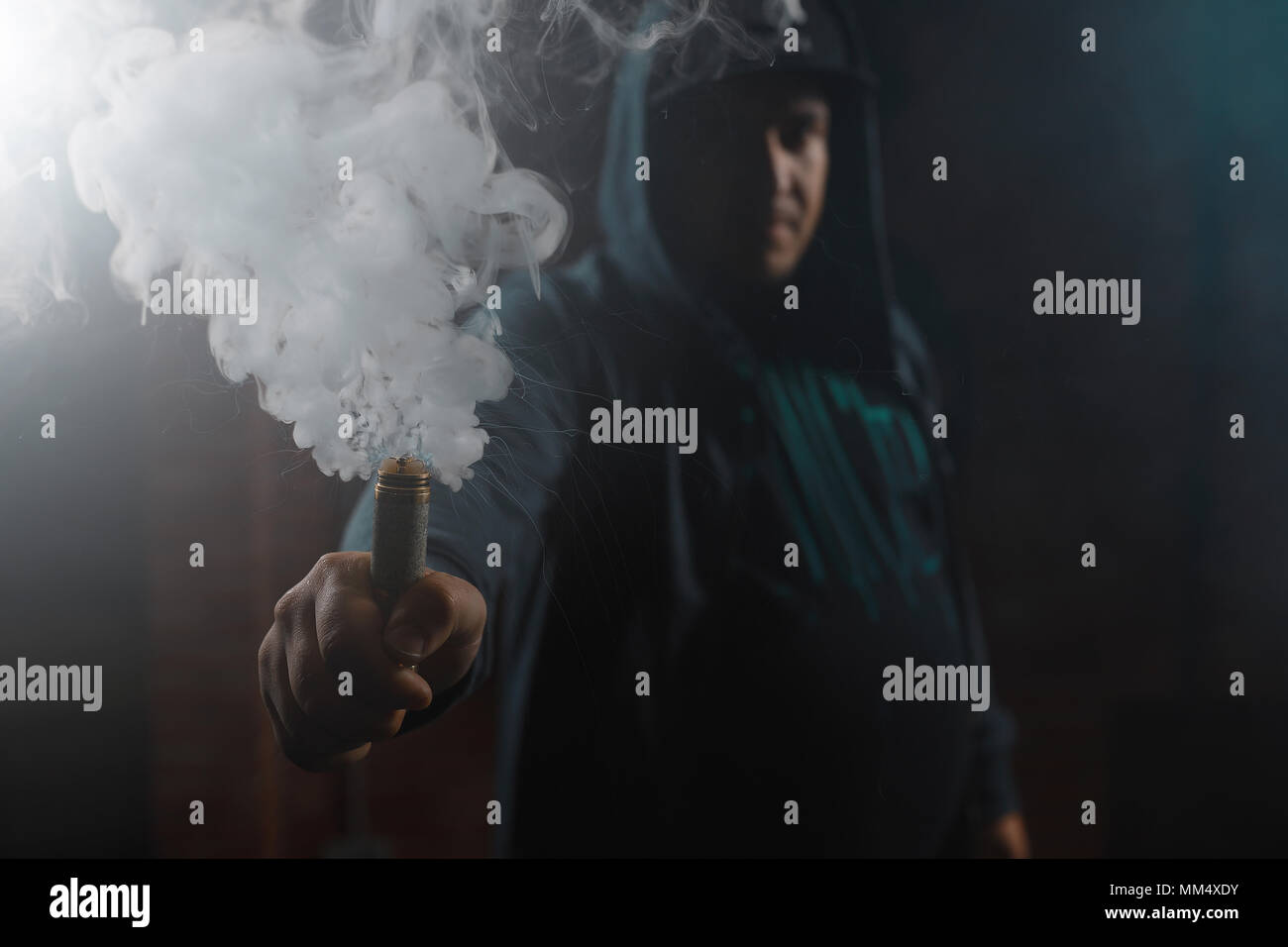 Dripper in one hand making a cloud of white, blue vapours. Friendly for vape shop posters and design. Vaping concept. - Stock Image