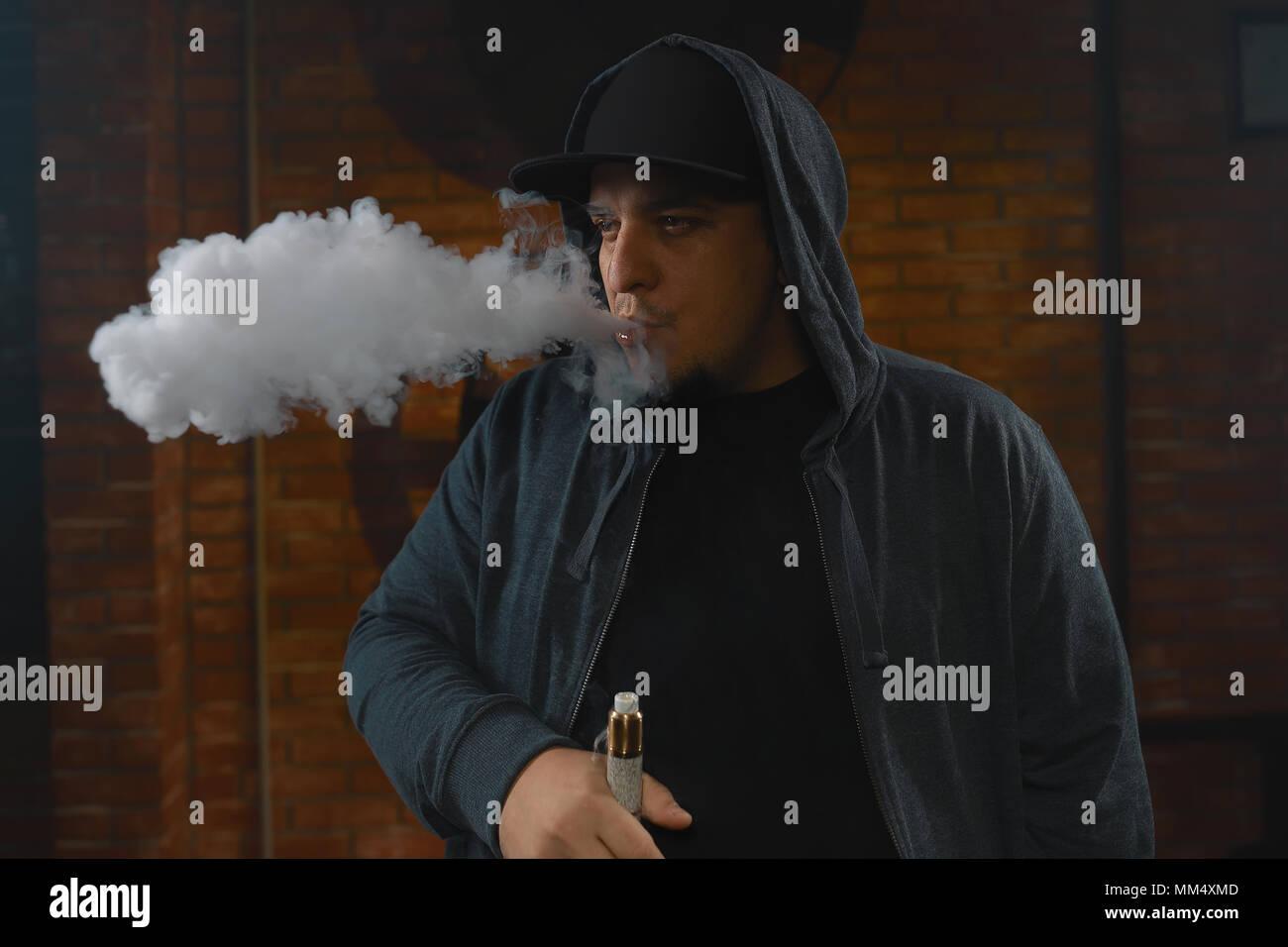 A cloud of vapor. Vaping man holding a mod. Brick background. Vape concept. Young man with beard vaping an electronic cigarette. Vaper hipster smoke v - Stock Image