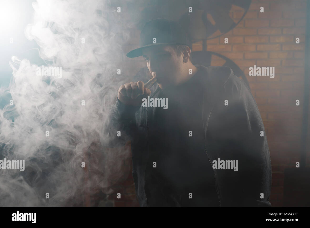 A cloud of vapor  Vaping man holding a mod  Brick background  Vape