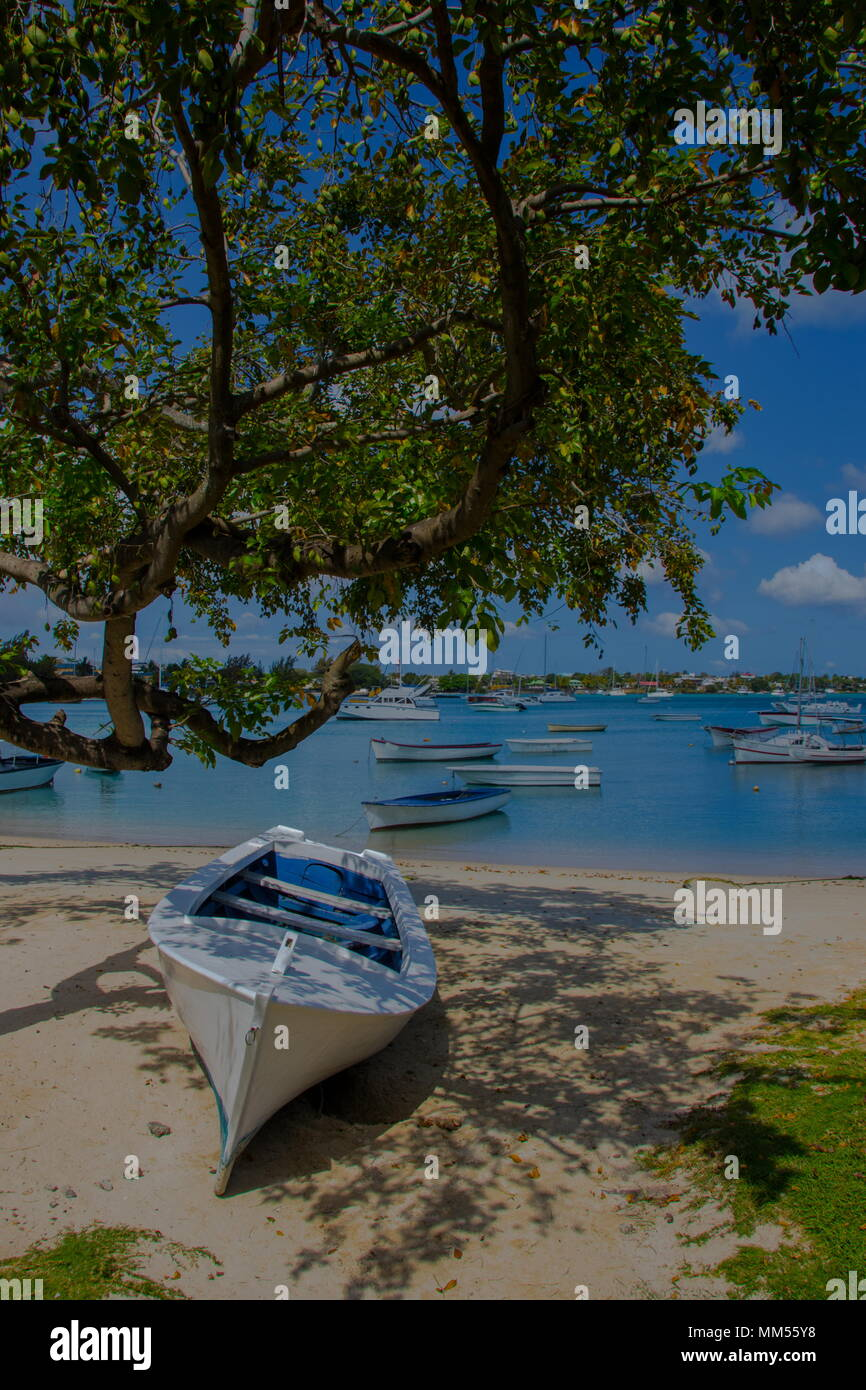 Grand Baie, Mauritius - tropical island romantic getaway scene with small pleasure craft moored on an azure colored bay image with copy space - Stock Image