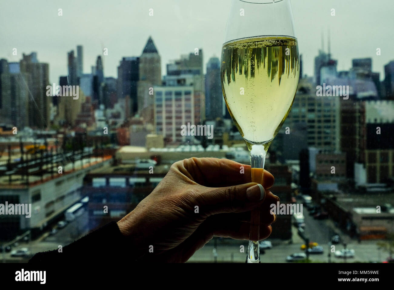 A woman holds a wine glass reflecting the skyline on the
