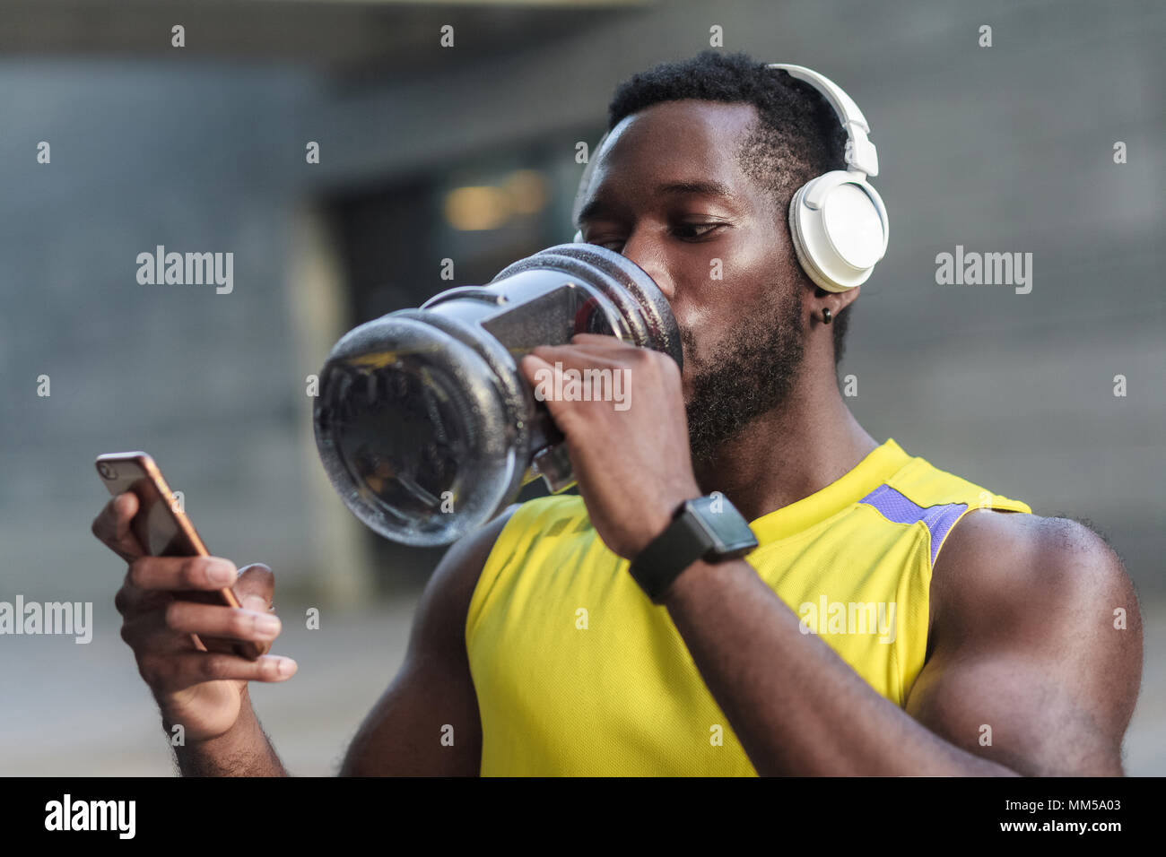 Active lifestyle. Strong african man drinking water after hard workout. Posting in instagram, looking at monitor new smartphone - Stock Image