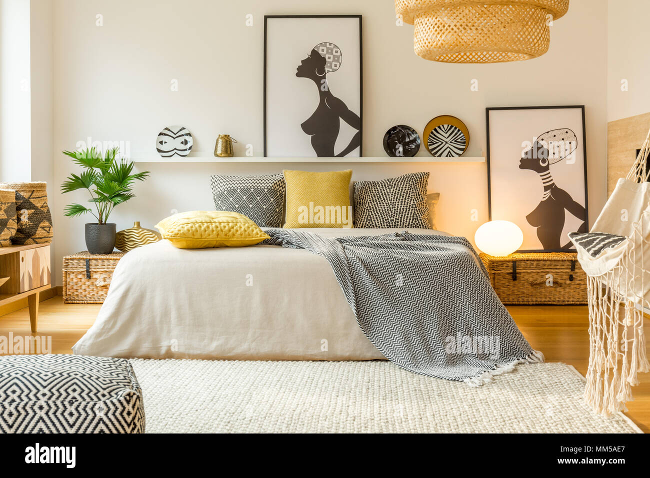 Yellow And Patterned Pillows On Bed In Modern Warm Bedroom Interior With Posters And Plant Stock Photo Alamy
