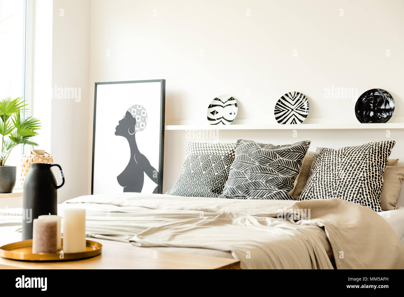 Patterned plates on shelf above bed in monochromatic bedroom interior with poster