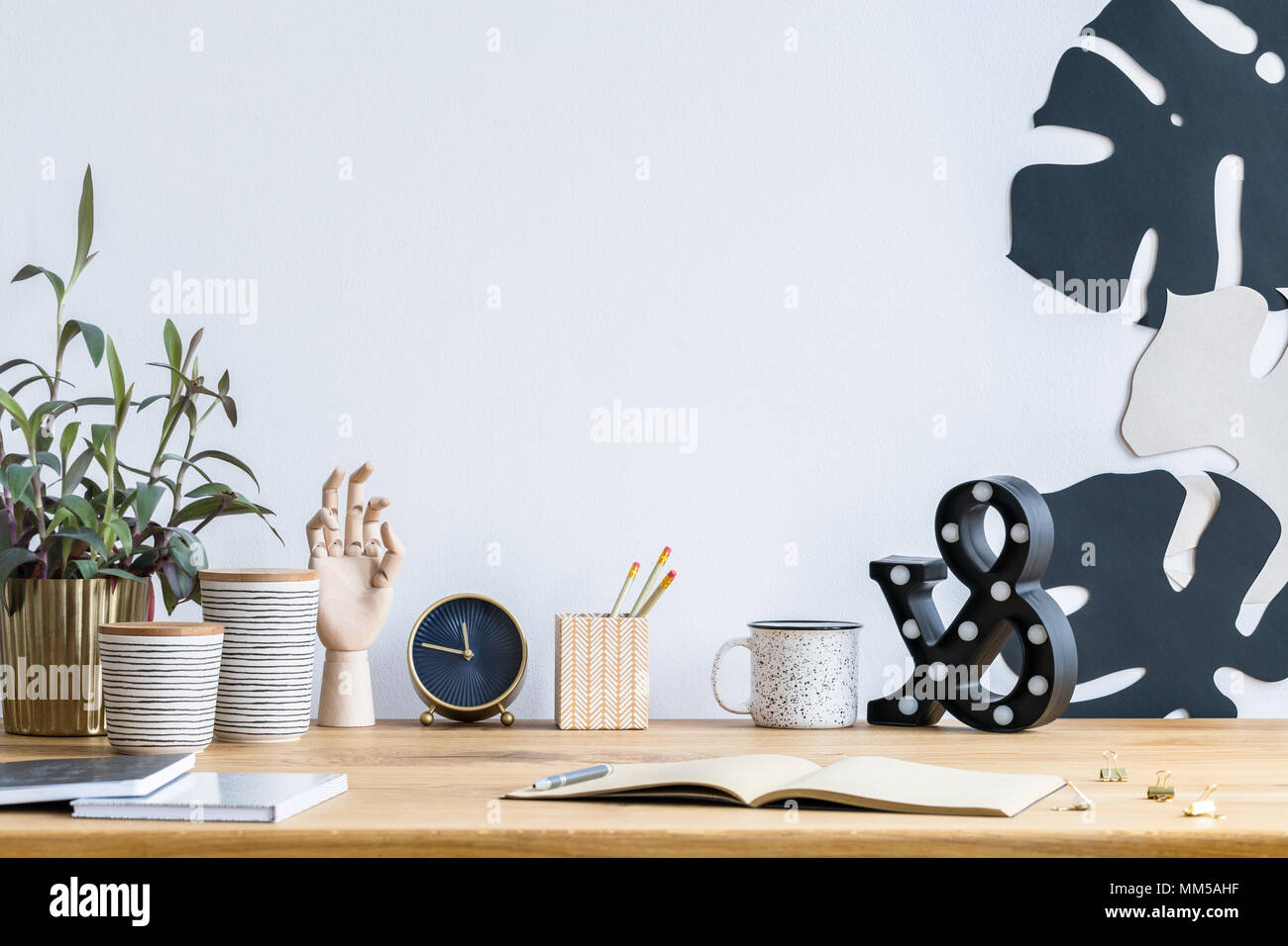 Messy desk with a plant in a golden pot, wooden hand, clock and leaves on the wall - Stock Image