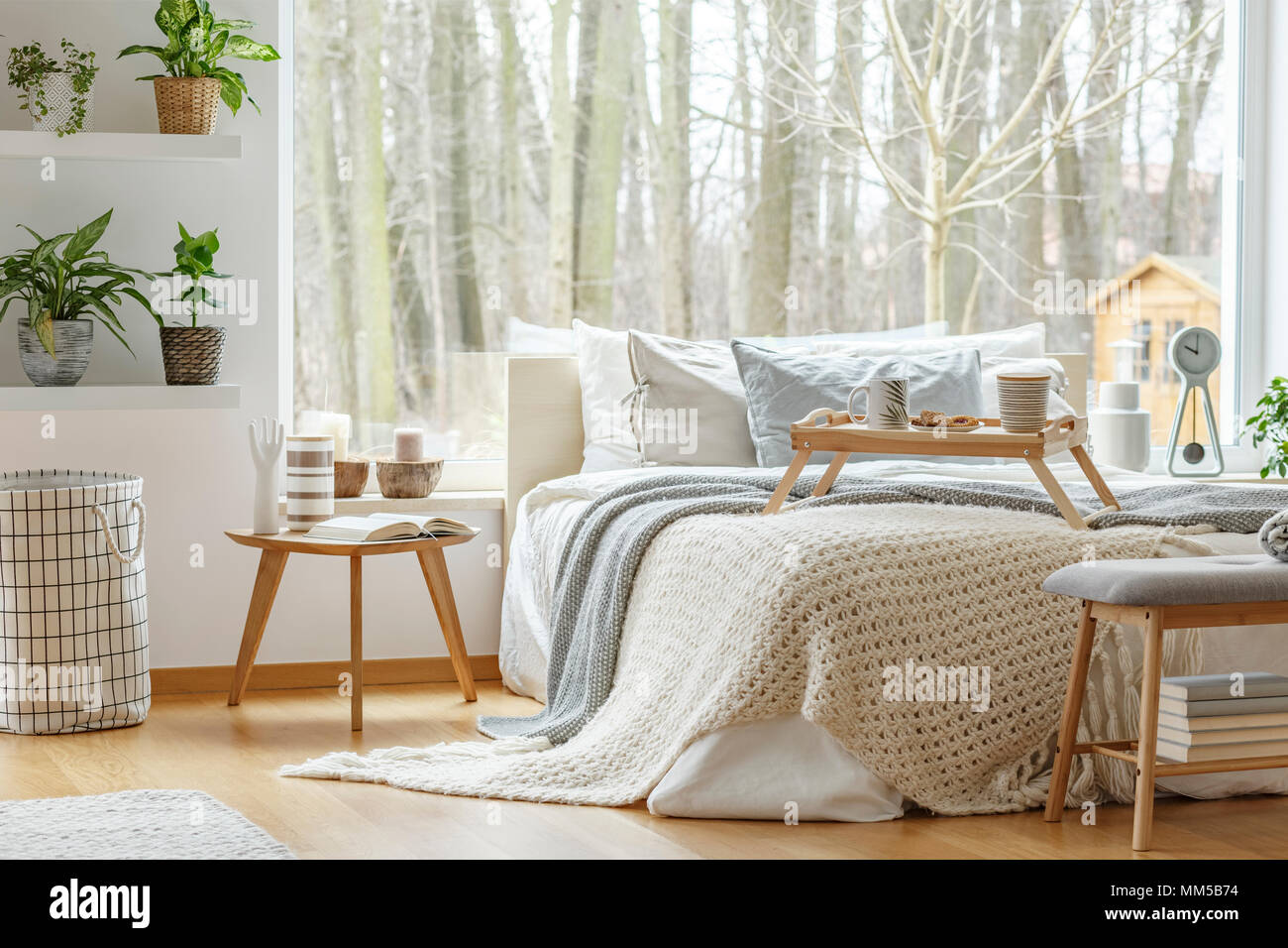 Book On Wooden Table Next To Bed In Minimal Bedroom Interior With Plants  And View On Forest
