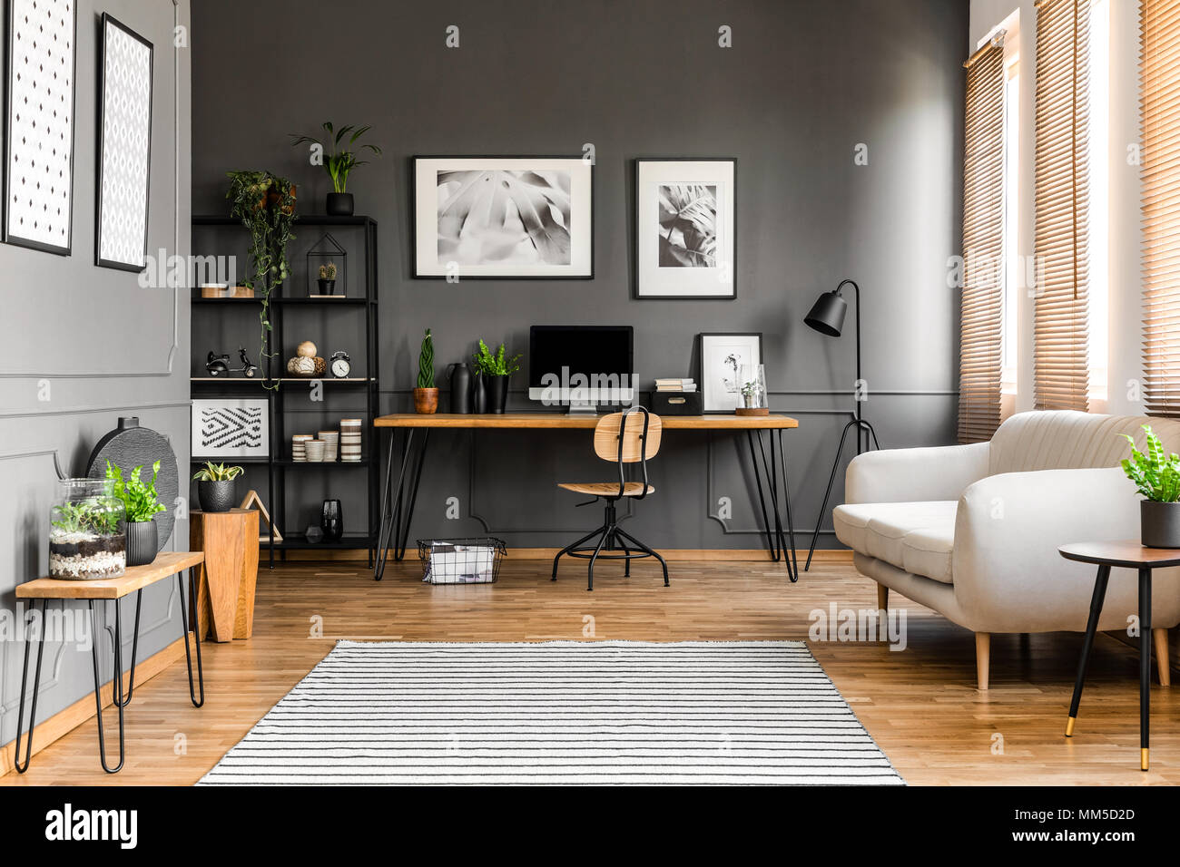 Beige couch near wooden desk with computer monitor in grey freelancer's room interior with posters and plants - Stock Image