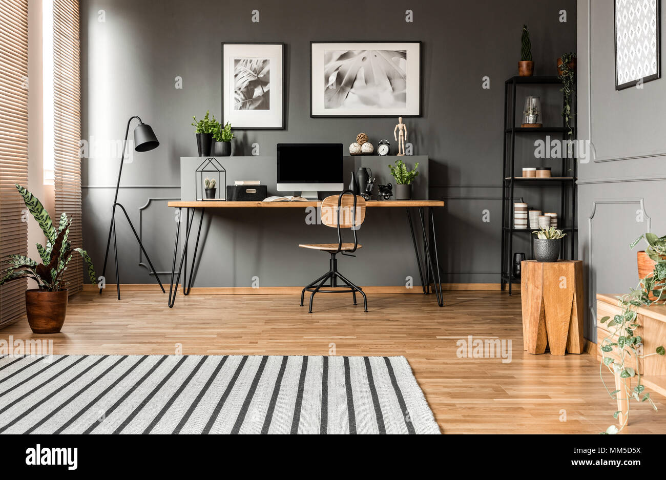 Plant on wooden stool near table with computer monitor in grey work area interior with posters - Stock Image