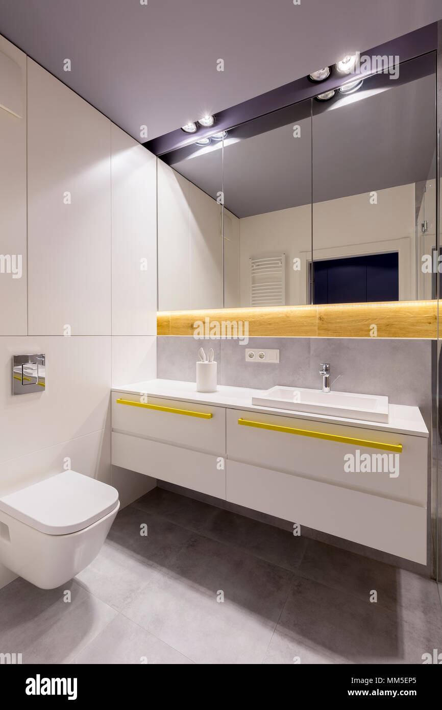 Mirror And Lights Above Washbasin And Cabinet With Yellow Accents In Modern Bathroom Interior Stock Photo Alamy