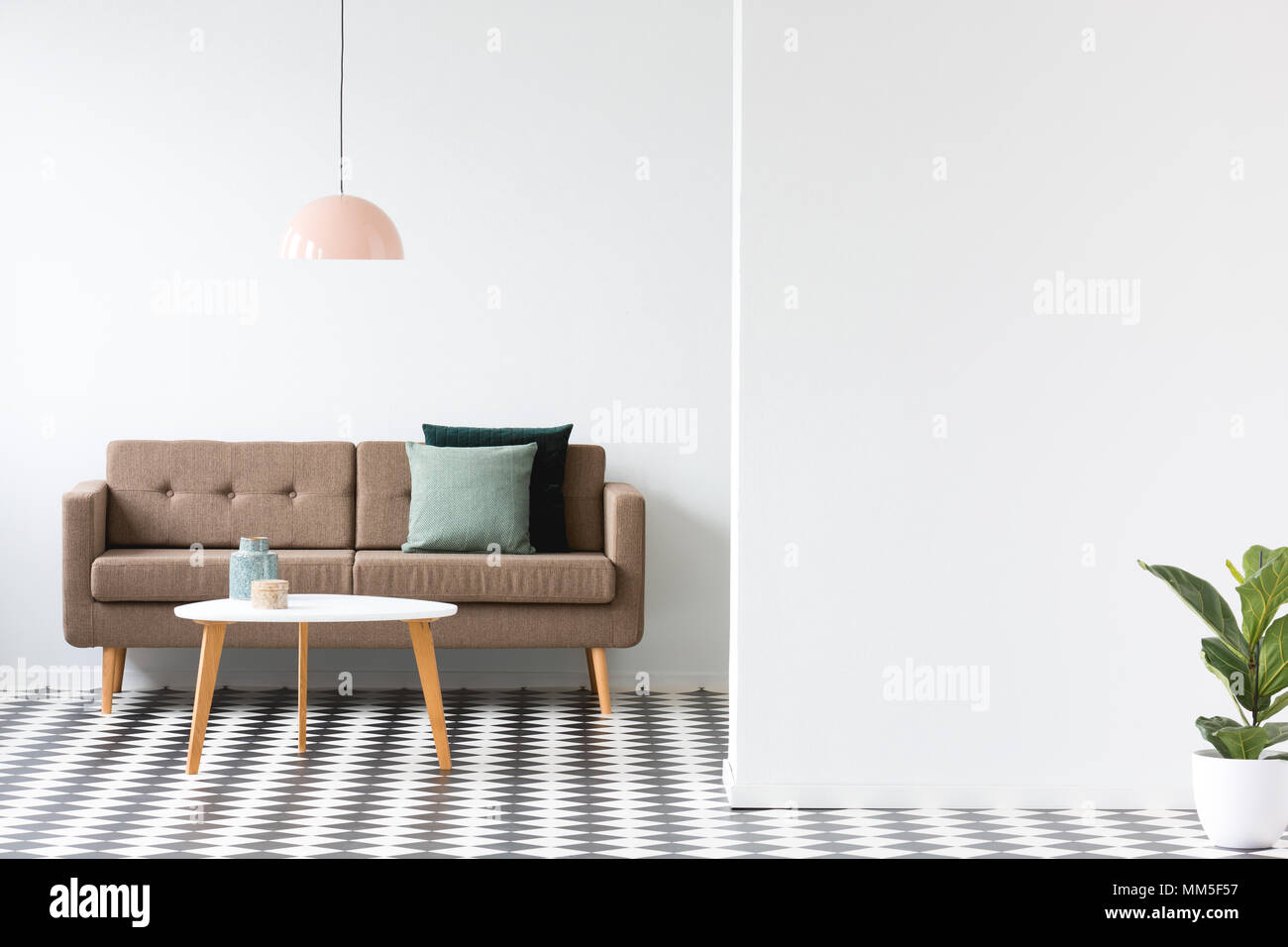 Round table in front of a brown sofa under pastel lamp in minimal ...