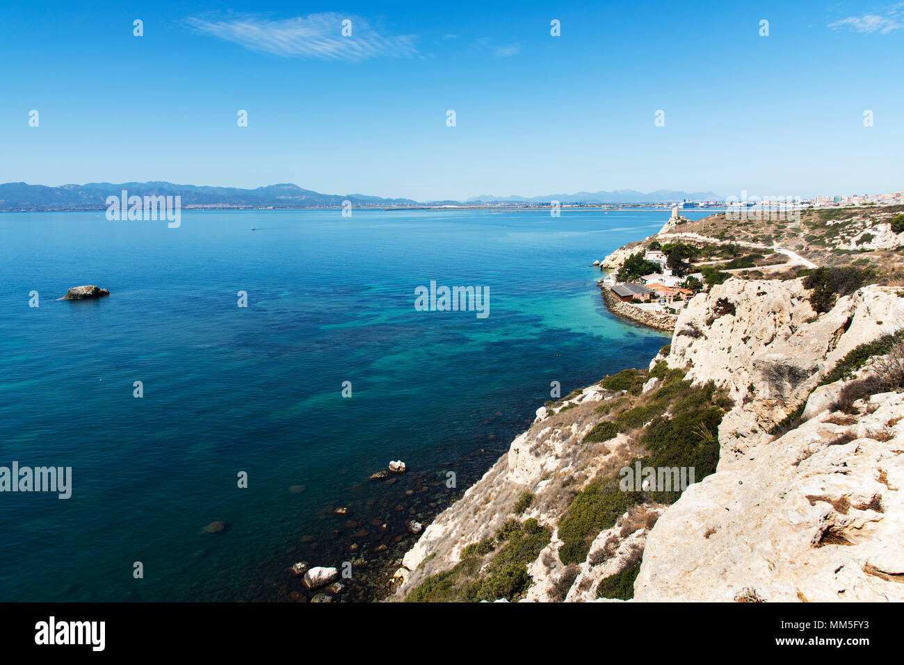a view of the coast of Sant Elia in Cagliari, Sardinia, highlighting the Prezzemolo tower on the right and the port of Cagliari in the background - Stock Image