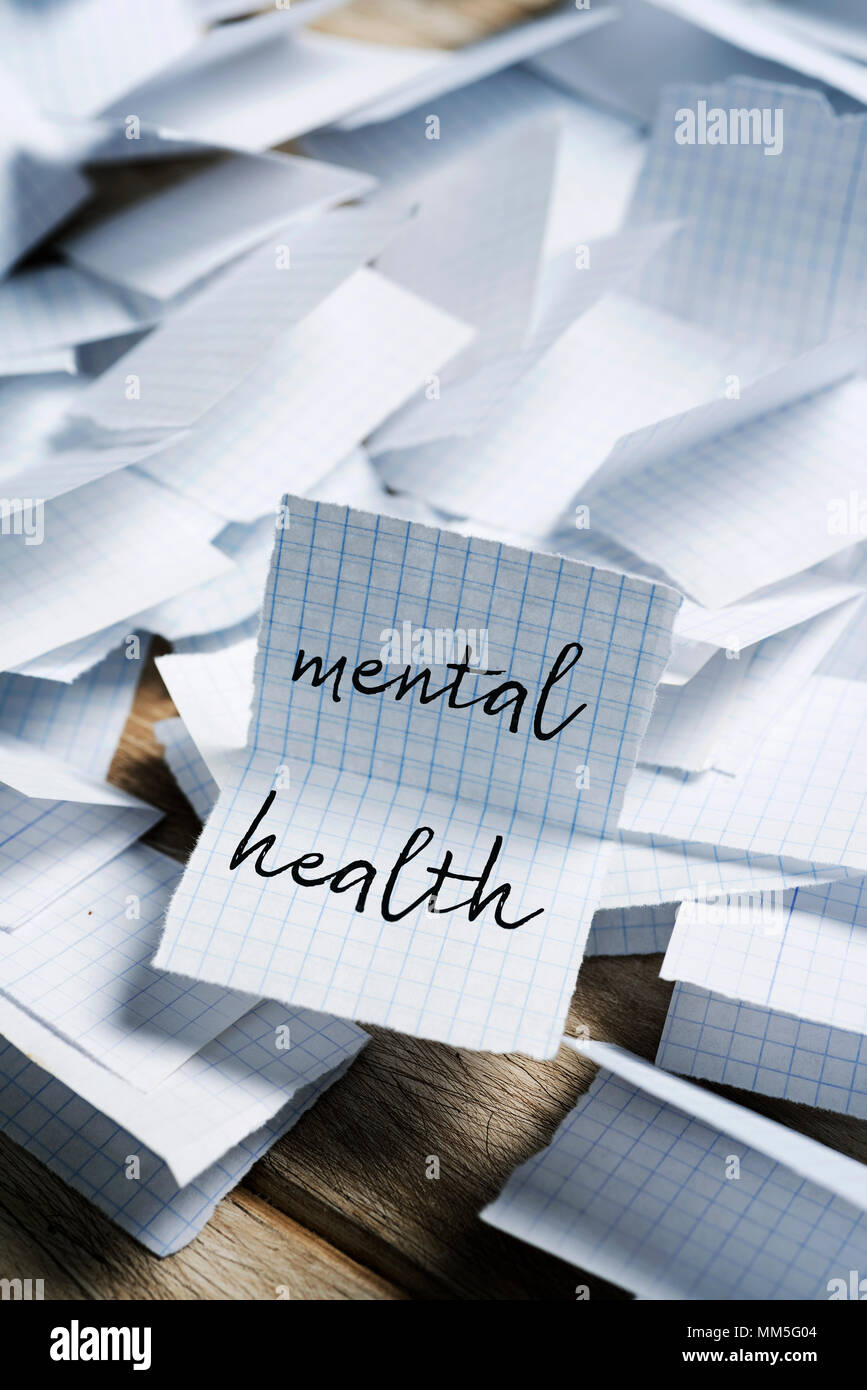 a pile of pieces of paper folded in half, and the text mental health in one of them unfolded in the foreground - Stock Image